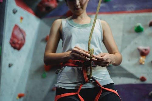 Crop female climber tying straps on safety belt