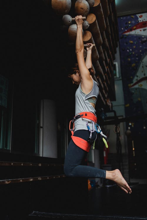 Side view full length fit sporty female in activewear and safety harness hanging on fitness bars before climbing training