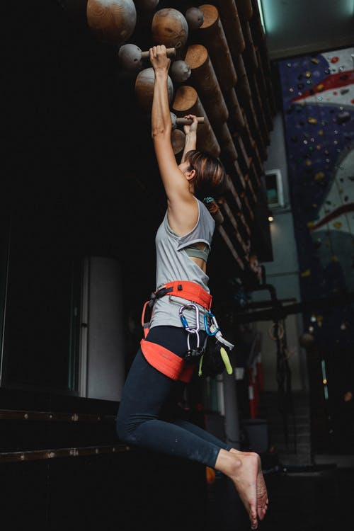 Faceless sportswoman doing hanging exercises in gym