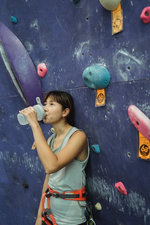 Side view young thirsty Asian female in activewear and safety harness drinking water from bottle after intense bouldering training