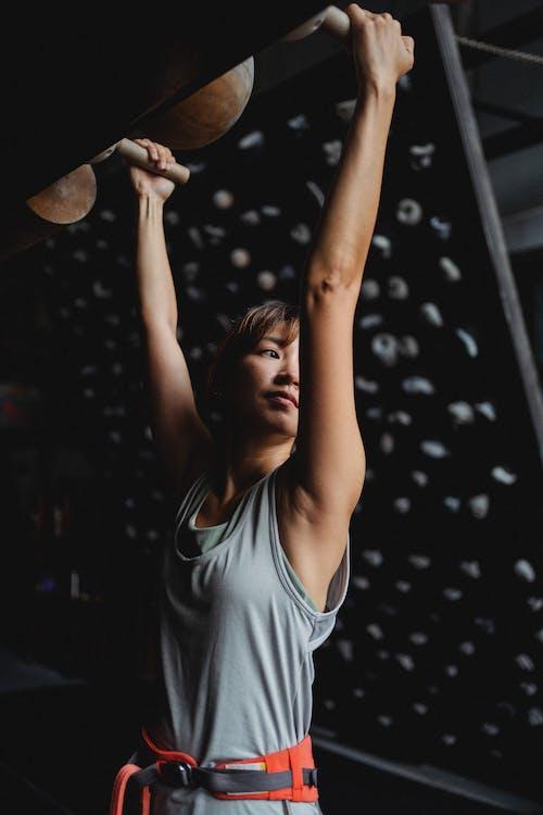 Positive Asian woman hanging on gymnastic equipment in climbing studio