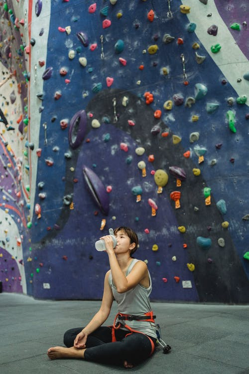 Full length tired Asian female climber in activewear sitting on floor near stiff climbing wall and drinking fresh water from bottle