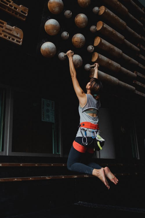 Faceless strong sportswoman hanging on fitness club equipment