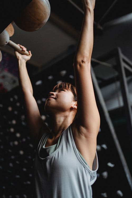 Determined woman hanging on gym equipment