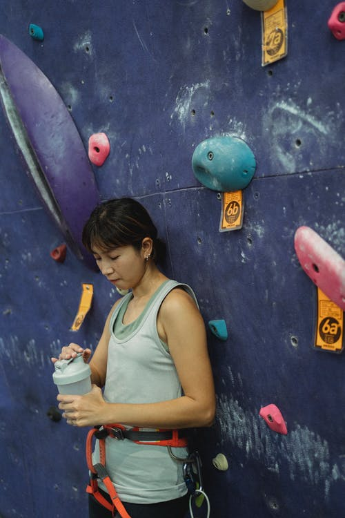 Side view fit thirsty Asian female wearing sportswear and safety harness standing near climbing wall and opening water bottle