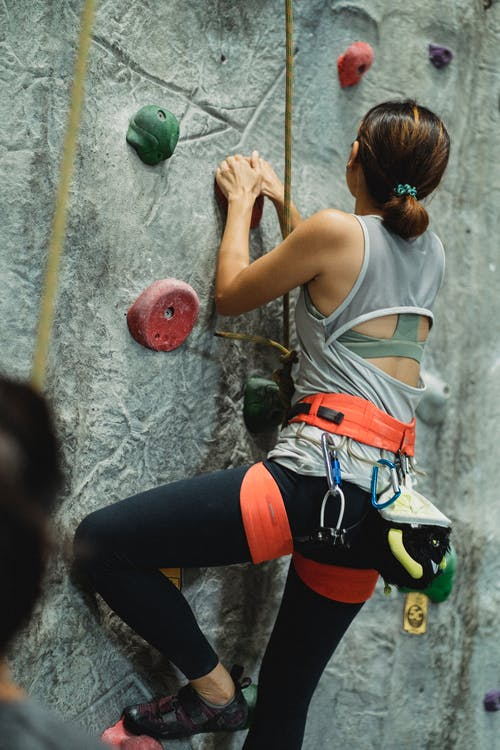 Back view of anonymous mountaineer in sportswear with safety belt climbing artificial rock near crop instructor