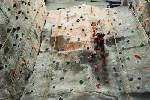 Asian alpinist ascending climbing wall during workout