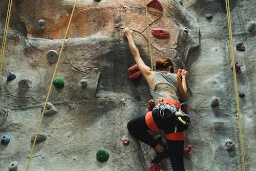 Unrecognizable climber ascending artificial rock during practice