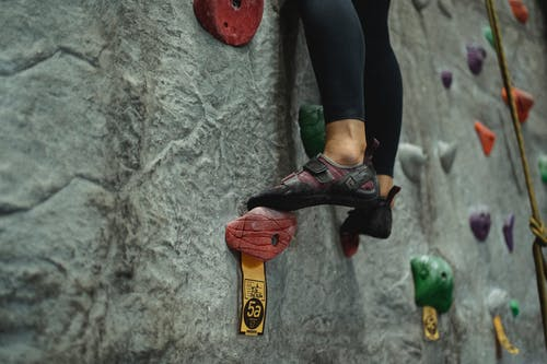Unrecognizable climber ascending climbing wall during practice