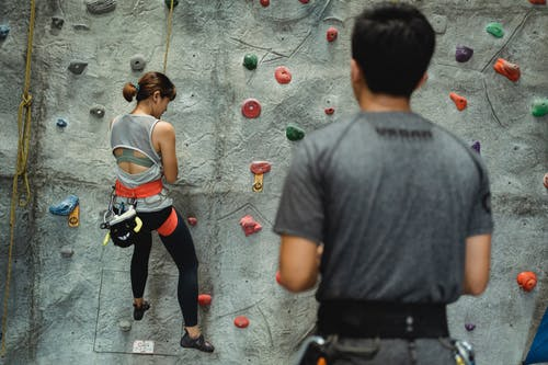 Back view of anonymous fit female alpinist in sportswear with safety harness climbing artificial rock near ethnic instructor