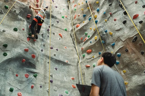 Low angle back view of unrecognizable male instructor and fit female alpinist climbing wall with holds