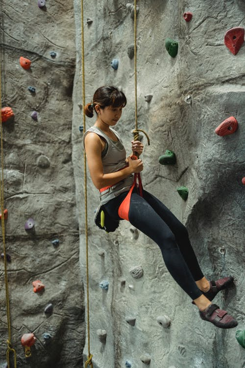 Side view of slender ethnic female hanging on special climbing rope near gray stony wall