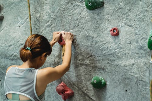 Young woman climbing on gray wall