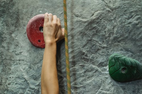 Crop anonymous person training and touching climbing hold attached to stony rough gray wall