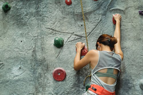 Strong brave woman with safety equipment climbing on wall