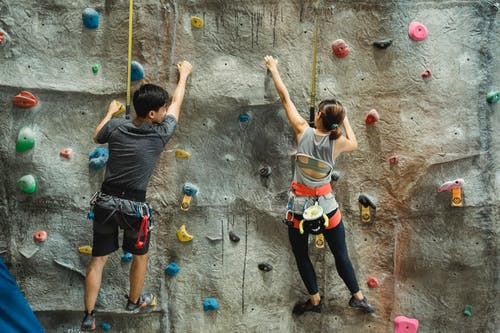 Back view of anonymous couple in activewear with safety equipment climbing rough gray rocky wall