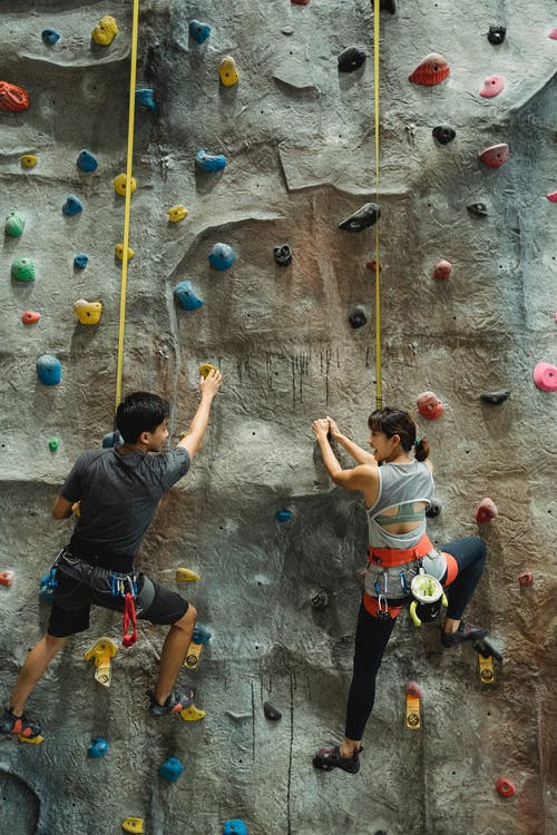 Back view of anonymous athlete couple with safety equipment talking and climbing gray stony wall
