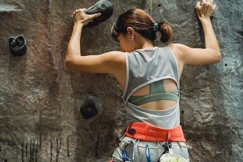 Sporty woman climbing on rocky wall