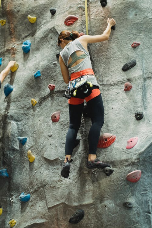From below of anonymous sportswoman in sportswear climbing on wall in climbing center during training and looking down
