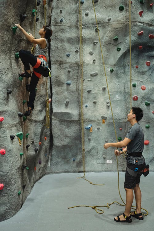 Full body of strong climbers mountaineering climbing wall with help of each other