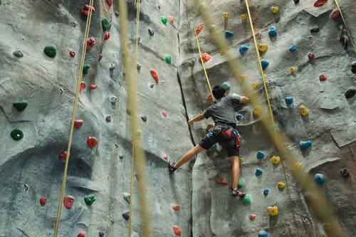 Unrecognizable climber practicing bouldering in gym