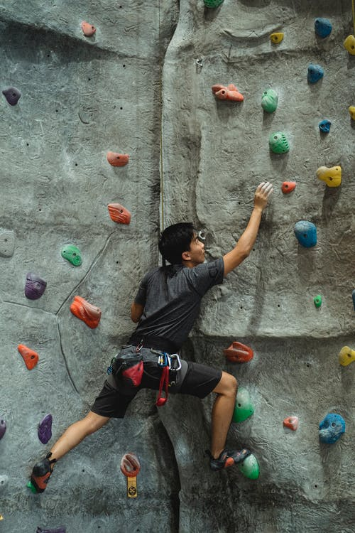 Concentrated male mountaineer in sportswear training on climbing wall in modern bouldering center