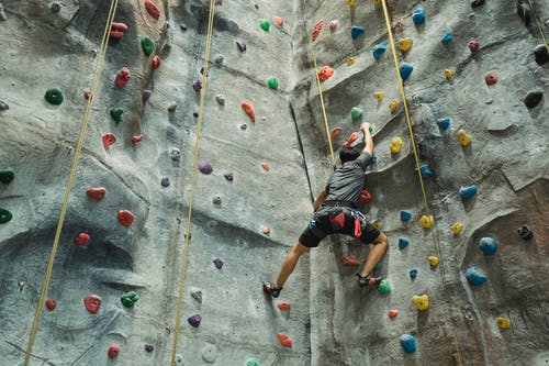 Unrecognizable man practicing climbing on wall
