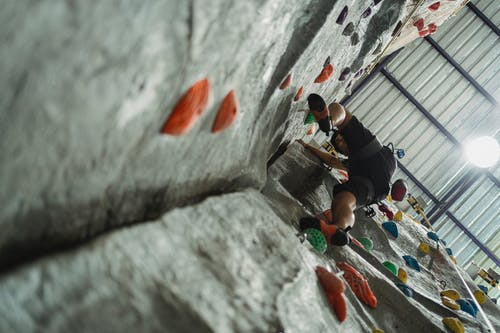 Low angle of unrecognizable male climber in activewear performing bouldering training with belay
