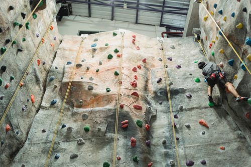 Unrecognizable climber ascending wall in gym
