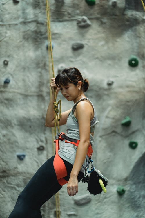 Side view of active female alpinist in sportswear hanging on belay while practicing climbing in gym