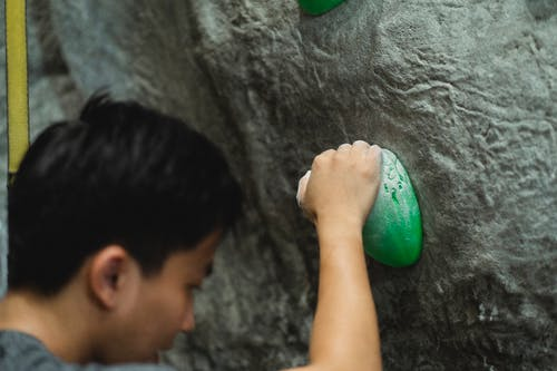 Faceless male mountaineer with hands in talc practicing bouldering on climbing wall in modern gym