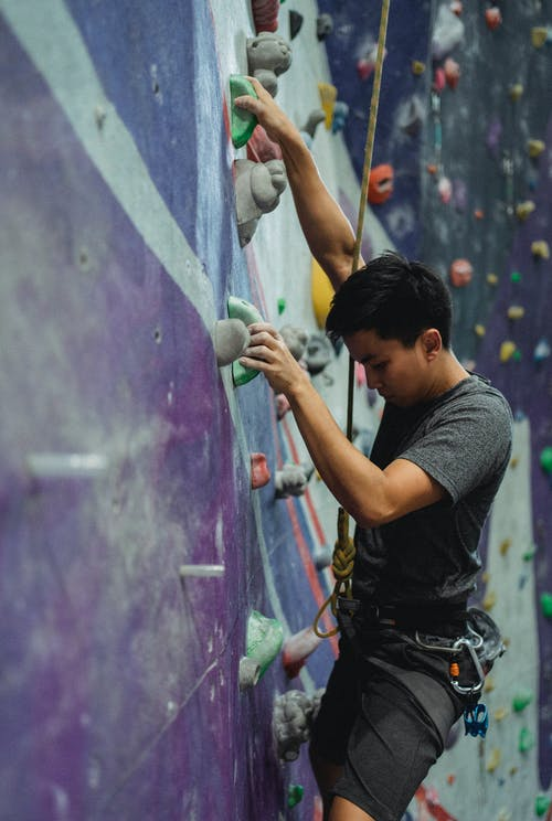 Side view of male mountaineer with belay training on climbing wall in gym