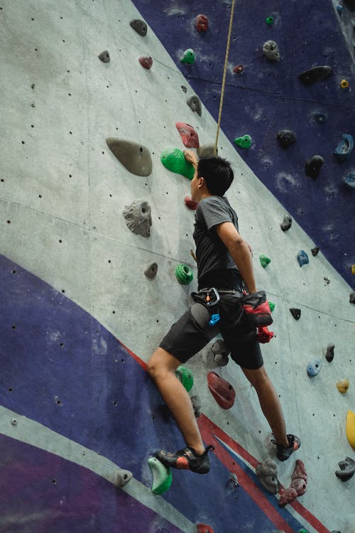 Confident climber ascending wall in gym