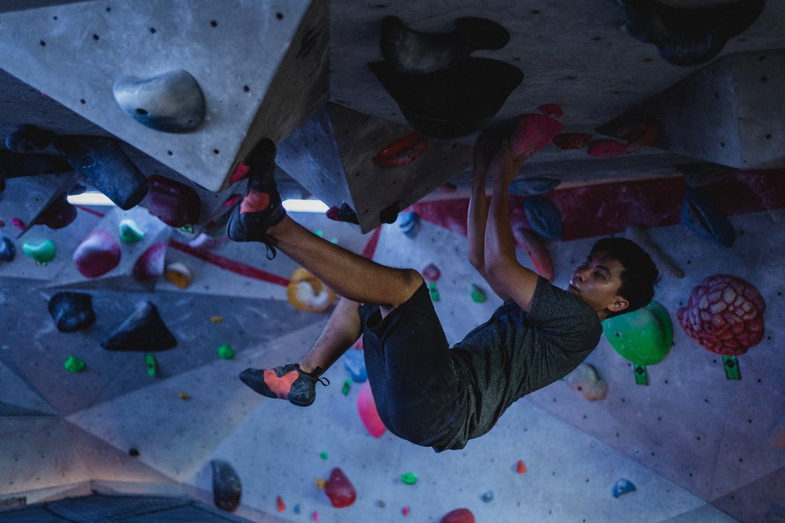 Side view of strong ethnic man practicing on climbing wall in modern bouldering center