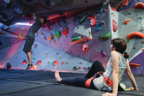 Asian man in climbing gym with girlfriend