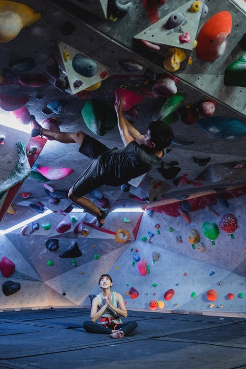 Active Asian guy hanging on roof of climbing surface in gym