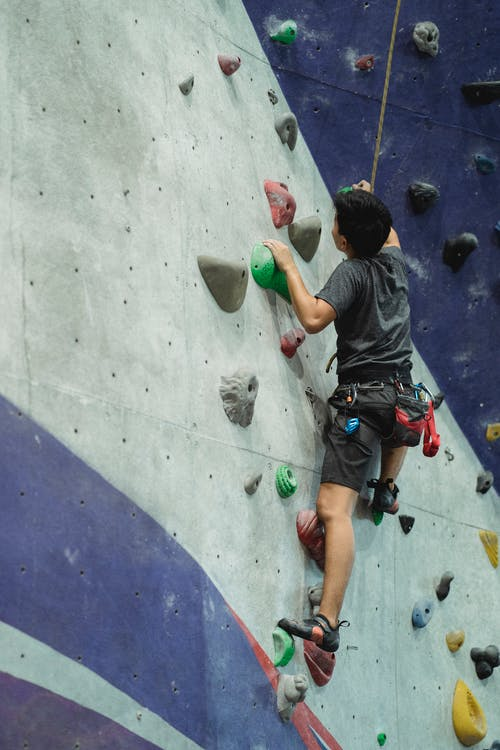 Back view of anonymous male climber with belay moving up on artificial wall during training in bouldering center