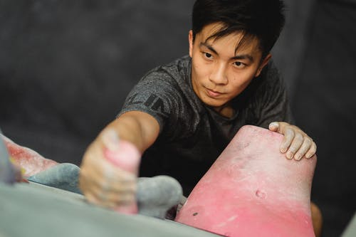 Young Asian guy ascending on climber wall in gym