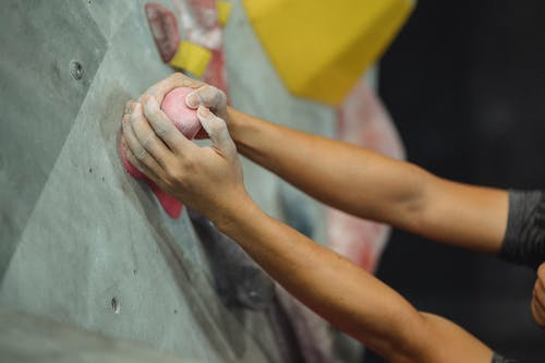 From above of crop male climber putting hands in talcum powder on pink climbing hold during training in gym