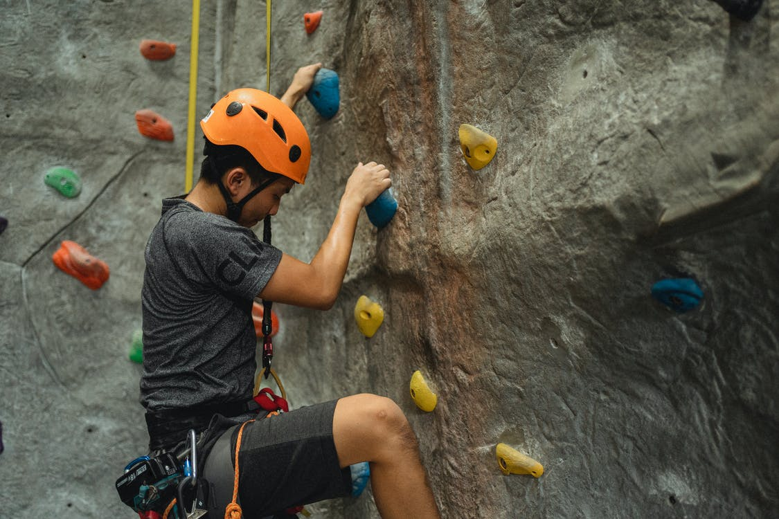 Side view of crop young Asian man in orange helmet and belay ascending on climbing wall during training in bouldering center