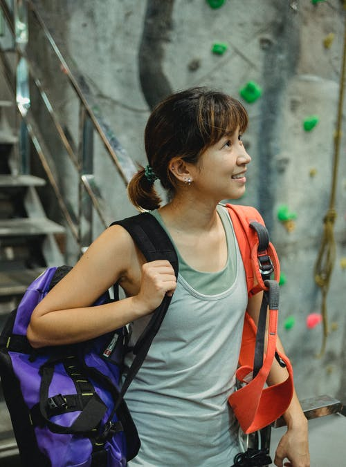 Happy Asian woman standing with safety belt in bouldering gym
