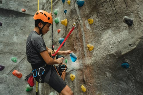 From below of side view of Asian male specialist in helmet drilling hole in blue climbing hold while hanging on safety rope near bouldering wall