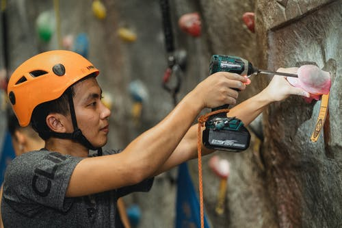 Side view of young workman in orange helmet attaching climbing hold with drill using screwdriver in bouldering gym