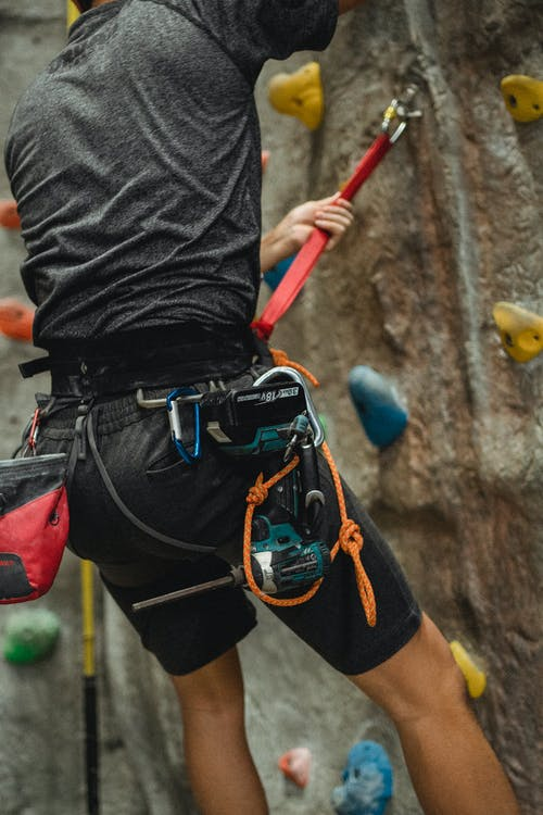 Unrecognizable male technician hanging on safety rope near climbing wall