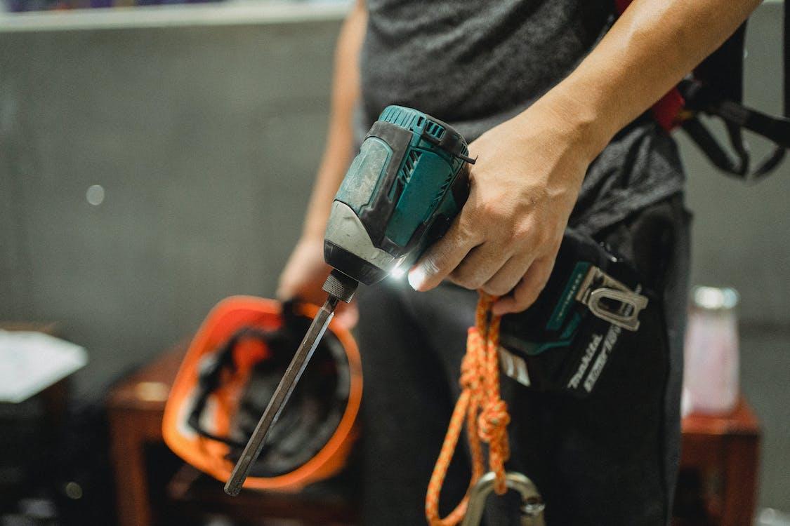 Riparatore Delle Colture In Piedi Con Un Cacciavite Funzionante E Casco Arancione