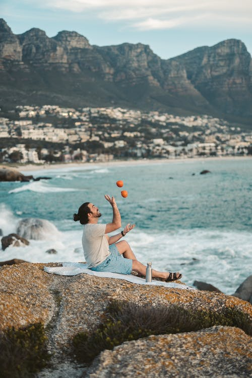 A Man Juggling Oranges at the Beach