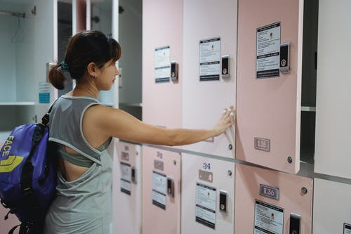 Side view of Asian female in sportswear closing door of modern locker with pink door before training in gym