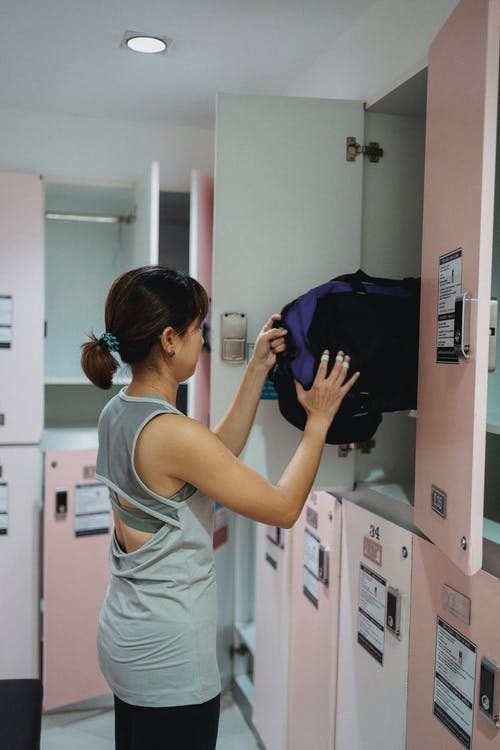 Young woman putting sportive bag in locker in changing room