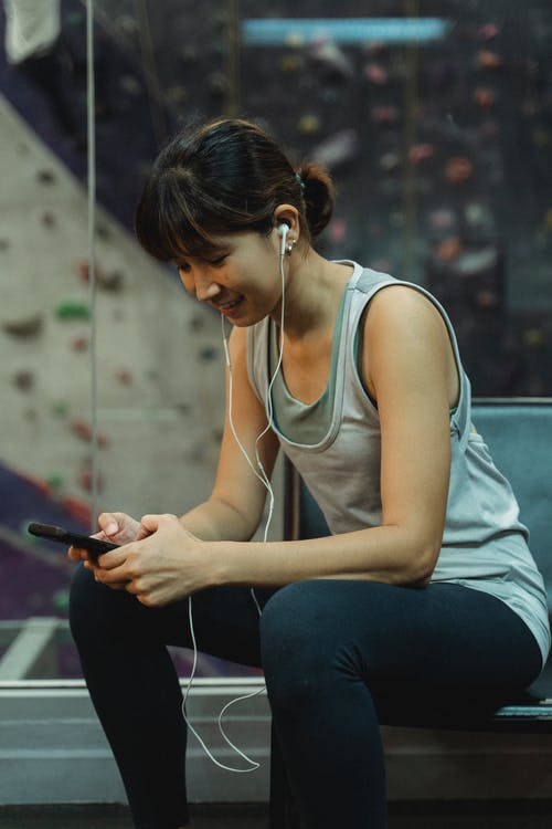 Happy young ethnic woman in earphones using smartphone during workout in gym