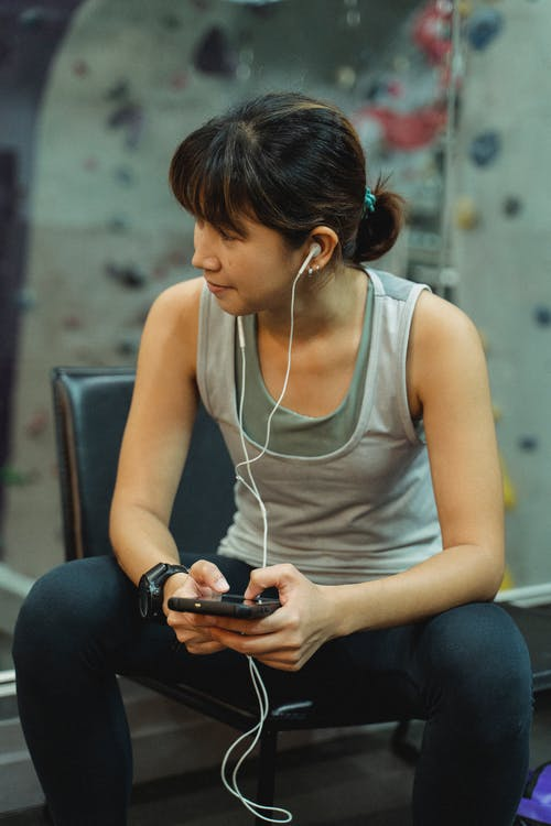 Young sporty Asian lady in activewear and earphones browsing mobile phone while relaxing on bench after workout in climbing gym
